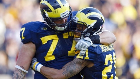 November 10, 2012; Ann Arbor, MI, USA; Michigan Wolverines offensive linesman Taylor Lewan (77) and wide receiver Roy Roundtree (21) celebrate a touchdown against the Northwestern Wildcats in overtime at Michigan Stadium. Michigan won 38-31.