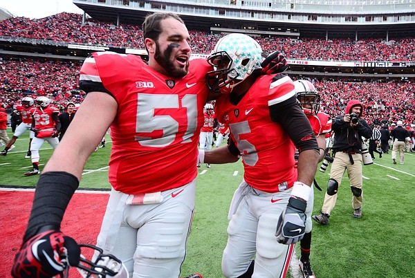 Nov 24, 2012; Columbus, OH, USA; Ohio State Buckeyes defensive tackle Joel Hale (51) celebrates with teammate Braxton Miller (5) after defeating the Michigan Wolverines 26-21 to go undefeated on the season at Ohio Stadium. Mandatory Credit: Andrew Weber-US PRESSWIRE.Credit: US PRESSWIRE