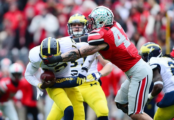 Nov 24, 2012; Columbus, OH, USA; Michigan Wolverines quarterback Devin Gardner (12) is sacked by Ohio State Buckeyes defensive lineman Nathan Williams (43) in the fourth quarter at Ohio Stadium. Mandatory Credit: Andrew Weber-US PRESSWIRE