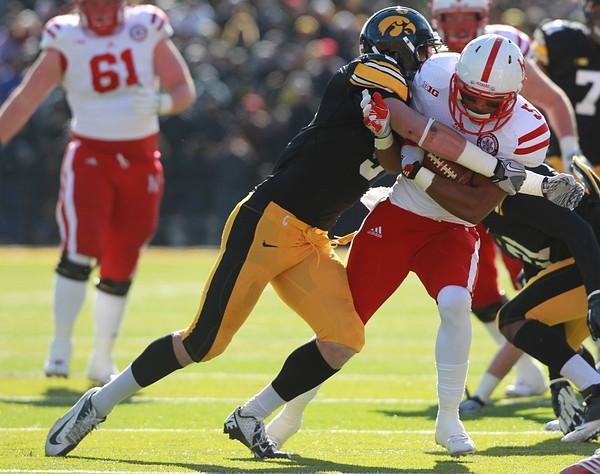 November 23, 2012; Iowa City, IA, USA; Nebraska Cornhuskers running back Braylon Heard (5) is tackled by Iowa Hawkeye defensive back Tanner Miller (5) at Kinnick Stadium.