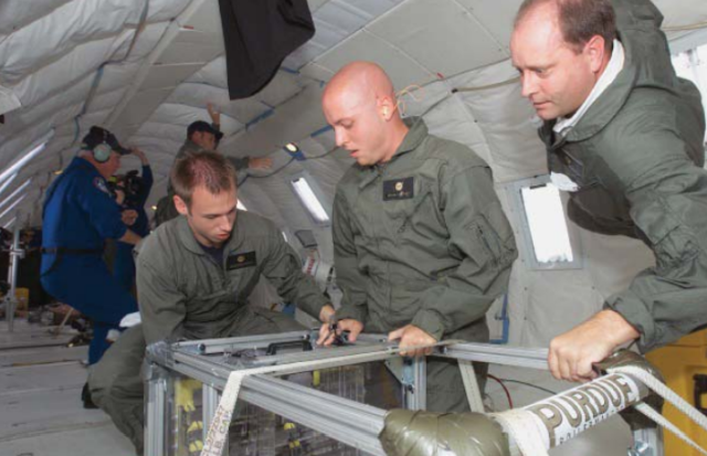 "Callicot (right) doing experiments on board the ""Vomit Comet,"" a NASA plane that simulates the zero-gravity environment."