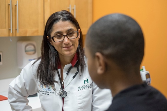 MSU's Dr. Hanna-Attisha chats with 9 year-old Jaquan during an examination. Photo courtesy of Michigan State