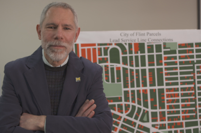 Prof. Kaufman with the map of Flint with water lines containing lead uncovered so far.