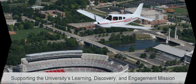 "A plane flies over the Ohio State University Stadium, the ""Horseshoe"""