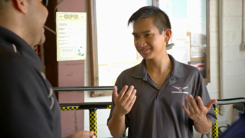 Raymart Tinio, a student of the Able Flight program at Purdue University, converses via sign language with an instructor.