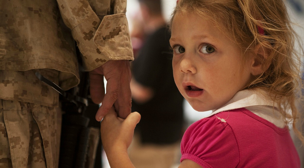 A young girl holds a soldier's hand