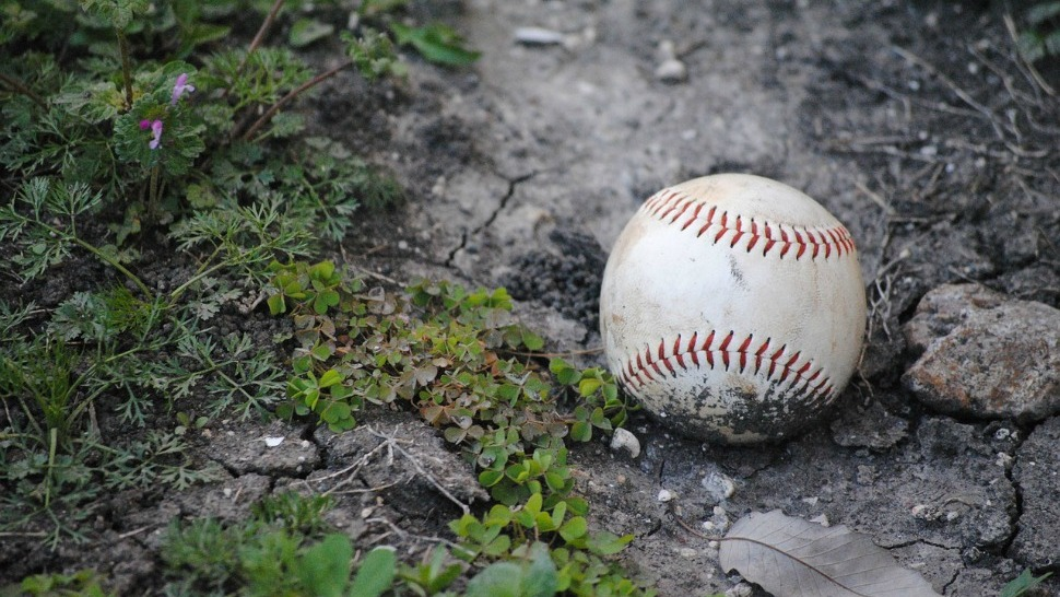 A well worn baseball sits in the dirt