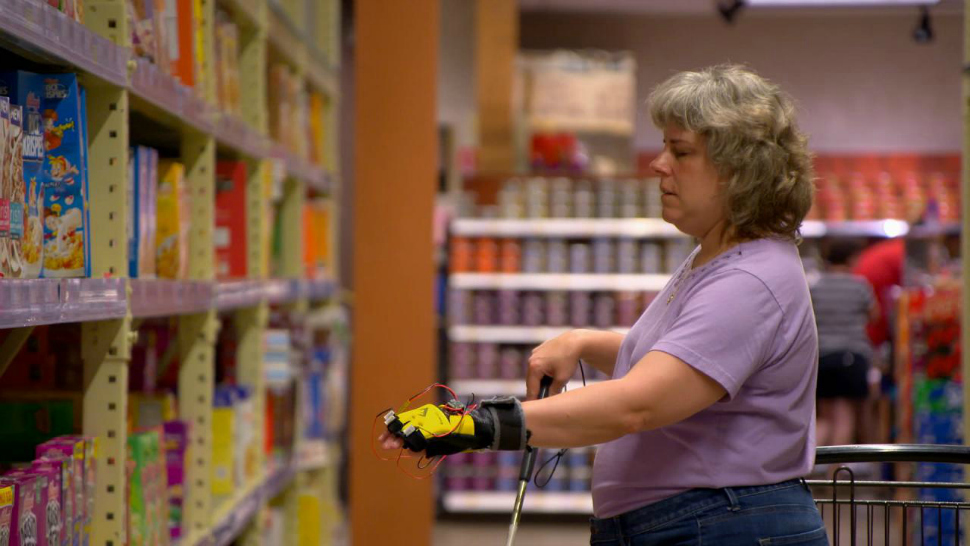 Penn State IT specialist Michelle McManus uses the Third Eye Project's glove cam to help her make a selection at a grocery store.
