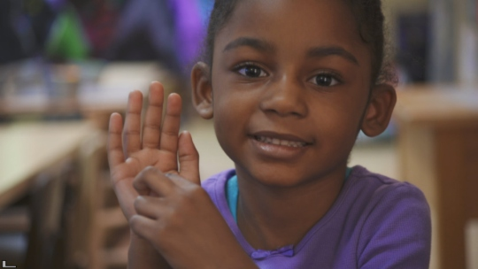 A little girl from Flint Michigan points to her hand.