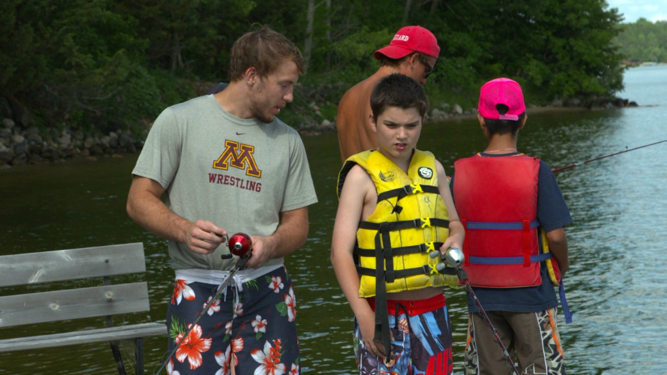 A University of Minnesoat student-athlete fishes with a camper at Camp Odayin