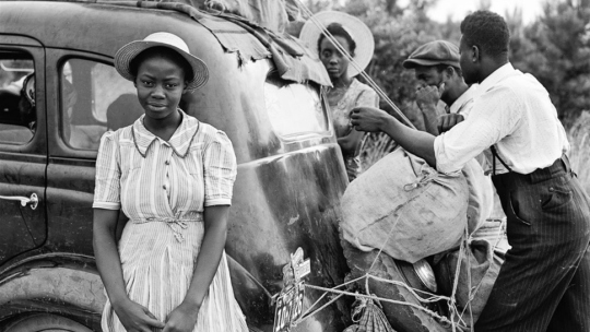 An historic photo of an African-American family loading up a car.