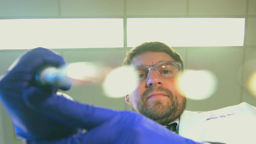 Northwestern University research physician C. Shad Thaxton pipes nanoparticles onto a glass plate