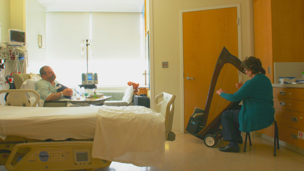 A certified musician performs in a University of Michigan hospital patient's room as part of the Gifts of Art program