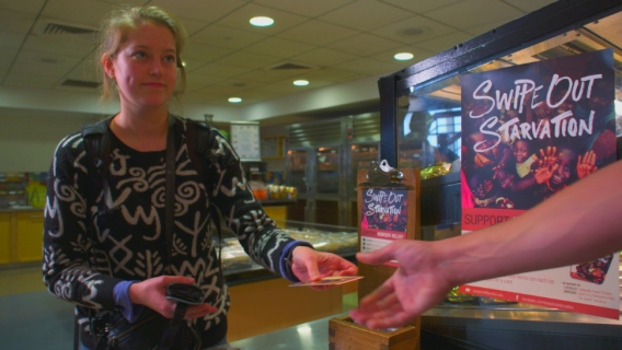 A Purdue University student purchases a Swipe Out Starvation card in a dining hall.
