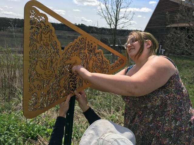 University of Wisconsin artists Liza Anna Kozik installing part of her prairie art exhibit.