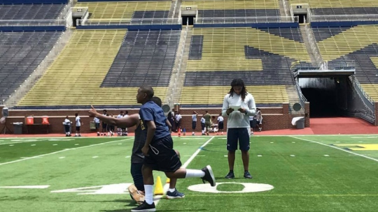 Students from the Youth Impact Program join University of Michigan football players on the field of the Big House stadium.