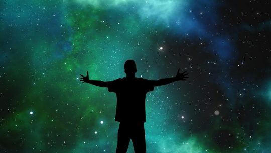 A silhouette of a person standing in front of a shot of the universe.