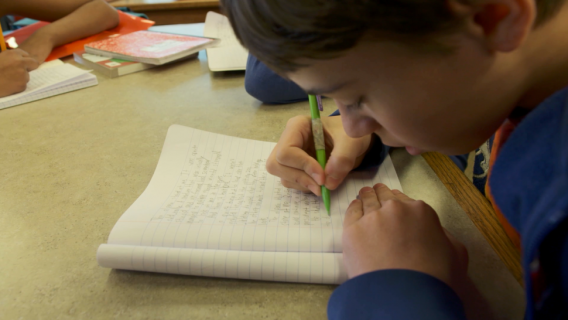 A student writing at the Iowa Youth Writing Project at the University of Iowa