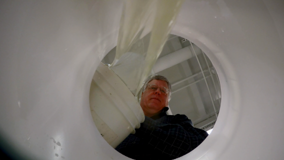 Purdue Engineering Professor Chad Jafverts pours water into a Maji Safi slow sand water filter