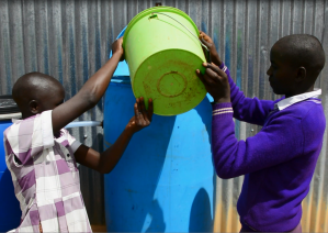 Students easily add water to their school's slow sand filter.