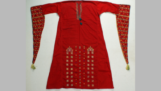Women's coats and dresses from the Quteife village in the Qalamoun mountains are famous for their distinctive use of red fabric and colorful embroidery on long triangular sleeves, neckline and skirt. These winged sleeves are especially found on garments worn by women while dancing, as they act like ribbons rippling through the air. Couching and overcast stitching in the embroidery in bright silk thread offer richly and finely executed handwork.