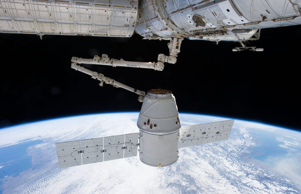A SpaceX Dragon Capsule attached to the International Space Station by the Canadarm