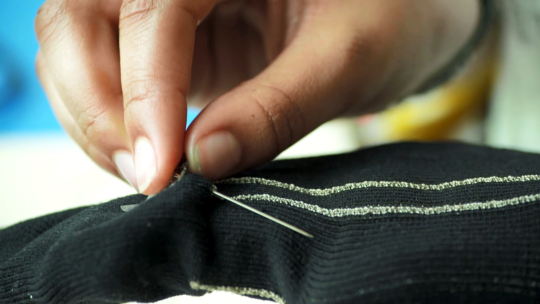 A student researcher sewing with computational textiles in Penn State's SOFTLAB@PSU makerspace