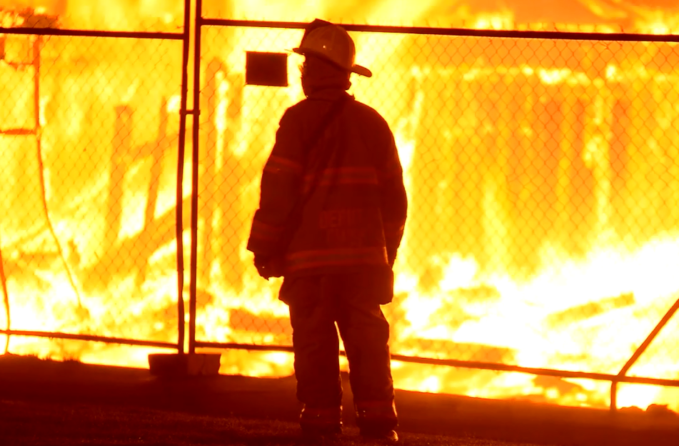 A firefighter in front of a burning building