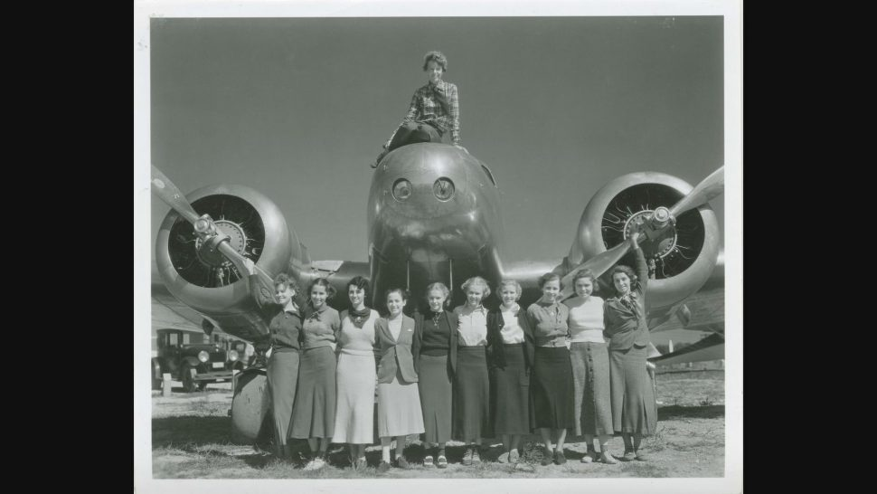 Amelia Earhart a a group of women in front of one of her planes