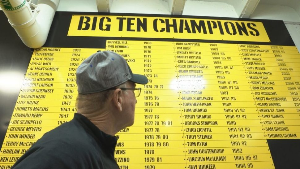 Famed University of Iowa wrestling coach Dan Gable looks at a board naming all of his Big Ten Champions