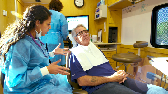 University of Minnesota dental student seeing a patient in the UCare Mobile Dental Clinic