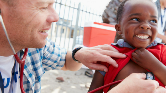 A doctor working with a smiling child