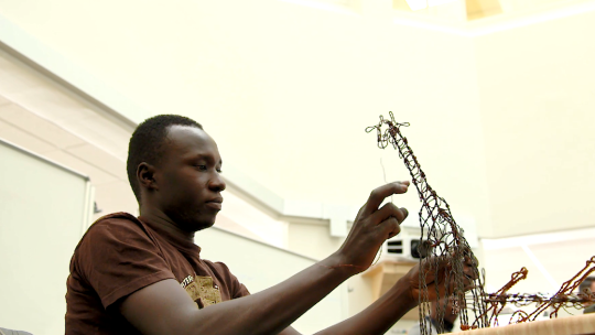 An artisan from Michigan State University's Snares to Wares Initiative crafts a giraffe sculpture from wire that was once a snare for poaching