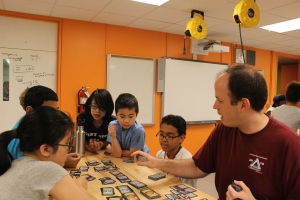 University of Illinois alum Daniel Zaharopol plays a math game with students in the BEAM program