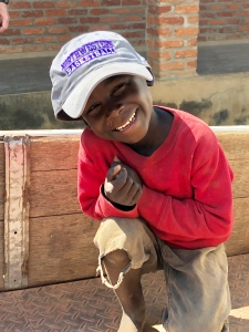 A child in Malawi wearing a Northwestern University basketball cap.