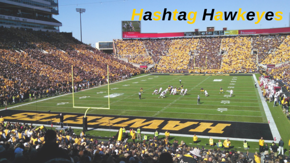 Hashtag Hawkeyes overlayed on an image of a University of Iowa Football Game