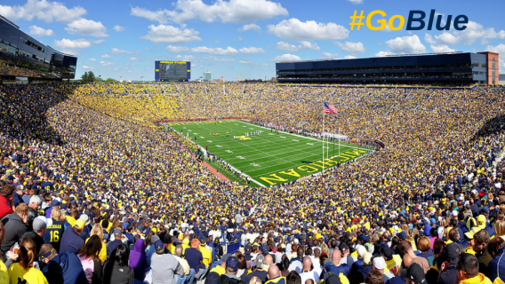 A shot of the University of Michigan Stadium with a crowd on football game day and the hastag Go Blue in the sky