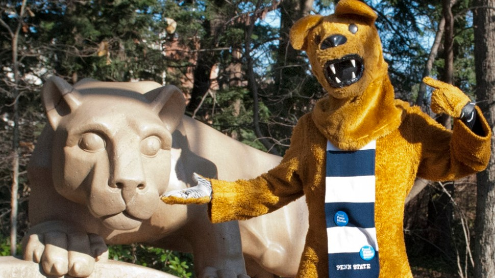 The Nittany Lion mascot visits the Nittany Lion statue. Penn State's University Park campus, Dec. 2012