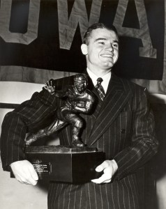 University of Iowa great Nile Kinnick poses with his 1939 Heisman Trophy