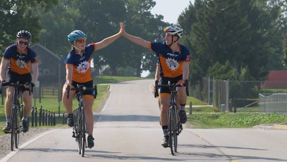 University of Illinois Illini 4000 riders high-fiving while riding their bikes