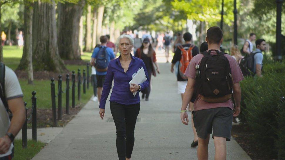 Penn State professor of anthropology Nina Jablonski walking on campus ina large group of people