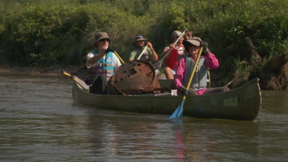 volunteers with Iowa project aware make their way down the a river with garbage collected in their canoe