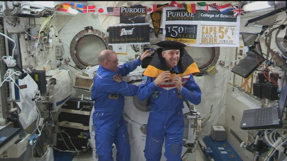 Purdue university alum and astronaut Andrew Feustel being awarded an honorary doctorate aboard the International Space station and being hooded by fellow boilermaker astronaut Scott Tingle