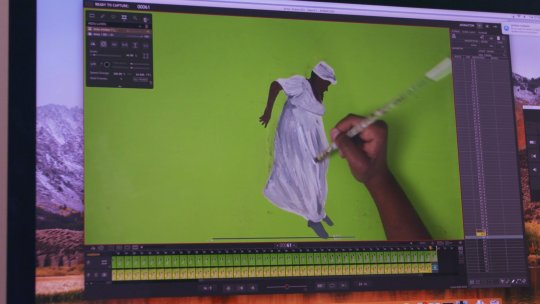 An animator works on painting a cell for the film Anna