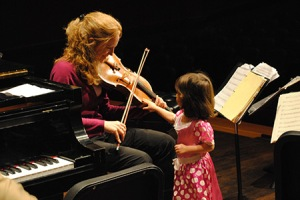 A child touches a violin during a Michigan State University Sensory Concert